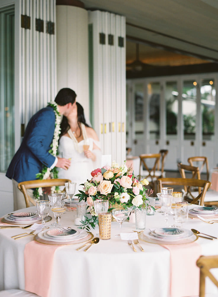Couple kissing near wedding reception tables