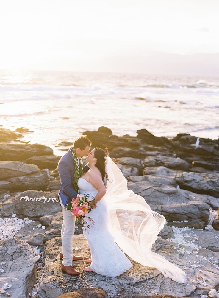 Bride and groom pose by the beach