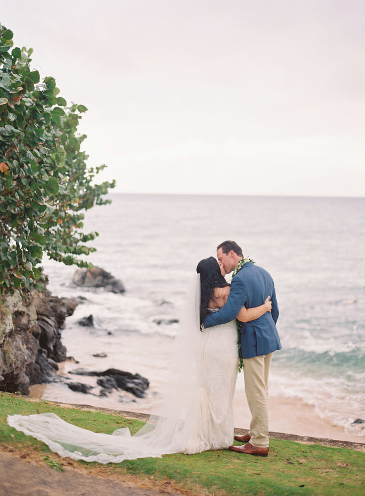 Bride and groom kiss by the ocean